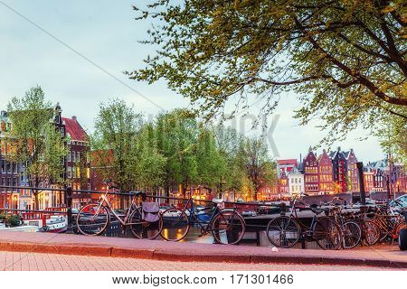 Beautiful tranquil scene of the city of Amsterdam. Bicycles along the street on the bridge over the canal