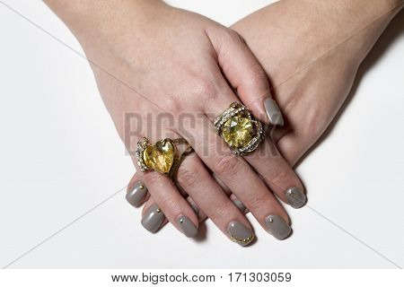 Two big yellow stoned rings with nice manicured fingernails. Soft focus poster
