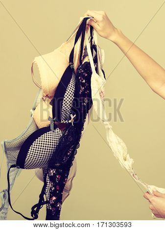 Female Hand With Many Bras To Wear