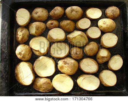 Baked potatoes in their skins on the old black pan.