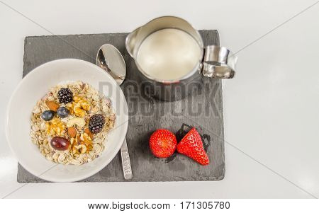 nutritious breakfast of oatmeal with fruit with a jug of milk on a black stone plate and purple hearts energetic food