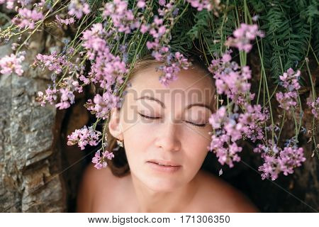 The girl with hair of flowers. A woman standing near the rocks. From mountain cliffs rising blue flowers, which appear to be part of the hair. Girl slightly naked.
