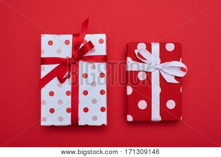 High angle of pair of polka dot gift boxes isolated over red flat layout. Resents wrapped with ribbons and bow tie