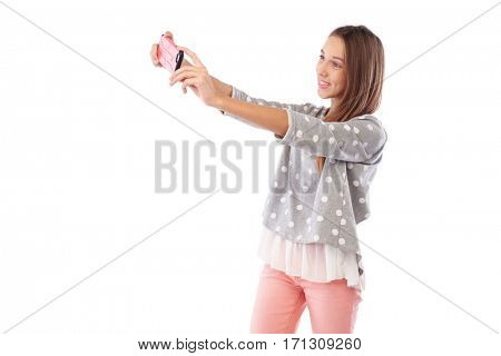 Mid side view of cute girl making selfie photo via smartphone isolated on a white background. Smiling and posing at the camera. Girl tries to make a good shot