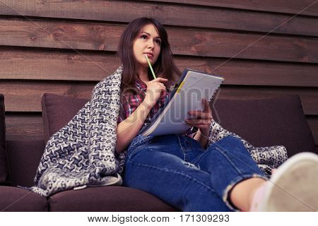 Side view of pensive girl making note in textbook. Sitting on the comfortable sofa at home. looking upwards. Covered with blanket