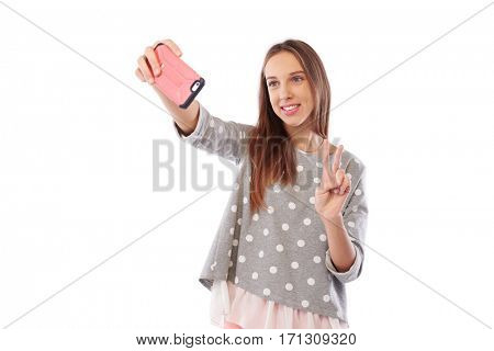 Mid shot portrait of a young attractive woman making selfie photo on smartphone isolated on a white background