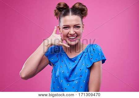 Close-up of pleasantly smiling model gesturing call me isolated over pink background. Funny female with two buns smiling at the camera