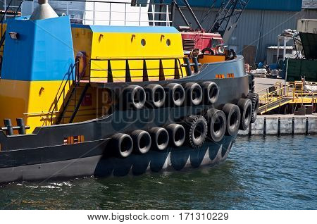 This is a closeup of a yellow and blue tug boat with tires lining the sides.