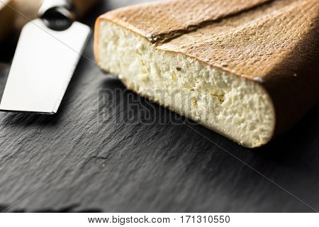 Chunk of cut goat smoked cheese with golden brown rind special knife on black stone board close up