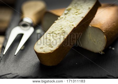 Chunk of smoked goat cheese and a cut thick slice with fork and knife in the background black stone board close up
