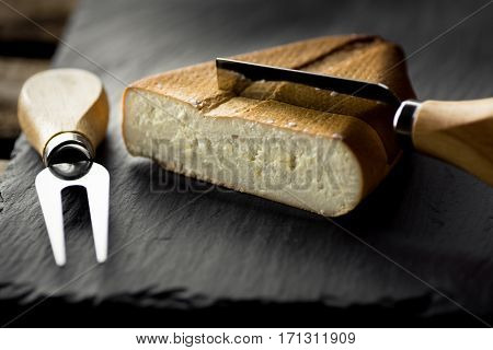 Chunk of smoked goat cheese with stuck knife and fork on black stone board gourmet meal close up