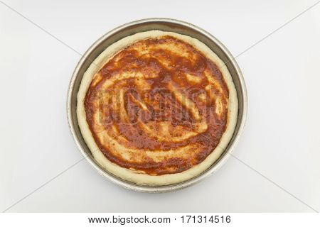 pizza dough and tomato paste on tray with isolated white background