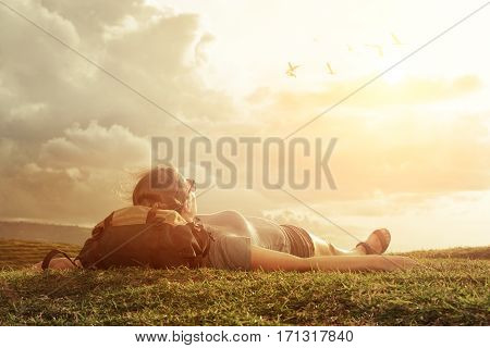 Carefree happy woman traveler with backpack lying on green grass on top of mountain edge cliff enjoying sun and clouds. Hiker think and relaxing after an excursion in the nature.