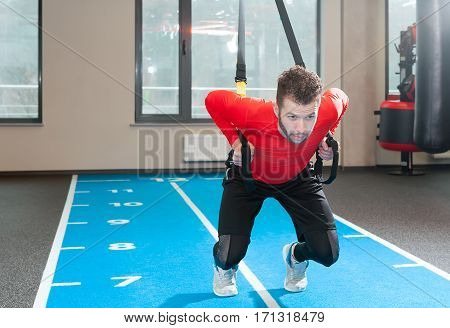 Crossfit instructor at the gym doing Excersise. Fitness man workout on the rings. Fitness man in the gym. Fitness style. Workout on rings. Sport and fitness. Crossfit workout