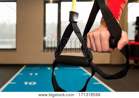 Male hands hold fitness straps in gym.