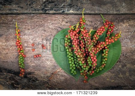 fresh green and red peppercorns with leaf isolated on old wooden background.