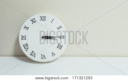 Closeup white clock for decorate show a quarter past three or 3:15 p.m. on white wood desk and cream wallpaper textured background with copy space