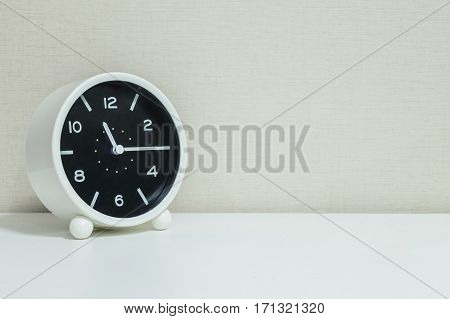 Closeup black and white alarm clock for decorate show a quarter past eleven or 11:15 a.m.on white wood desk and cream wallpaper textured background with copy space
