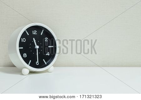 Closeup black and white alarm clock for decorate show show half past eleven or 11:30 a.m. on white wood desk and cream wallpaper textured background with copy space