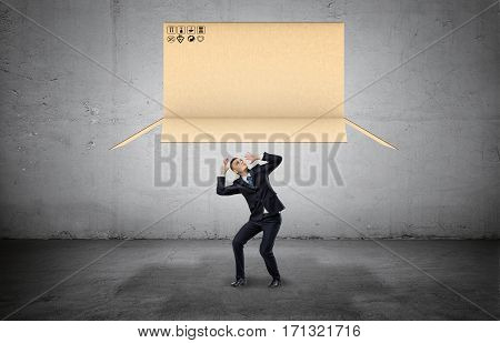 Businessman on concrete background cowering below a large open carton box falling on him. Business and success. Obstacles and limitations. Risk and danger.