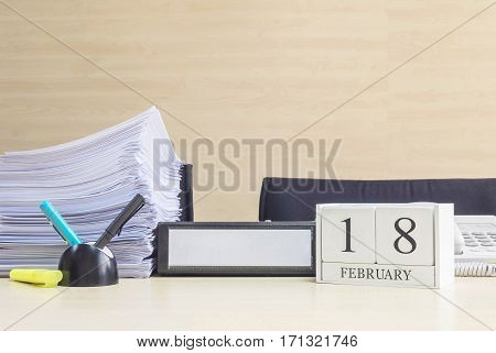 Closeup white wooden calendar with black 18 february word on blurred brown wood desk and wood wall textured background in office room view with copy space in selective focus at the calendar