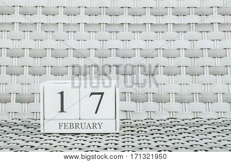 Closeup surface white wooden calendar with black 17 february word on blurred weave wood chair textured background with copy space in selective focus at the calendar