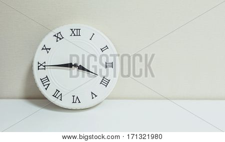 Closeup white clock for decorate show a quarter to four p.m. or 3:45 p.m. on white wood desk and cream wallpaper textured background with copy space