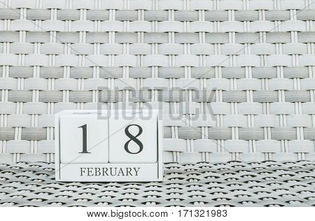 Closeup surface white wooden calendar with black 18 february word on blurred weave wood chair textured background with copy space in selective focus at the calendar
