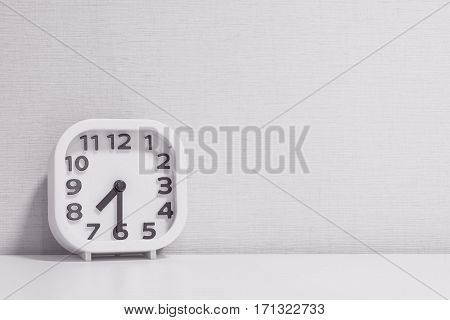 Closeup white clock for decorate show half past seven or 7:30 a.m. on white wood desk and cream wallpaper textured background in black and white tone with copy space