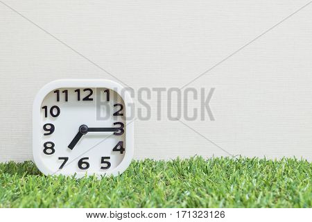 Closeup white clock for decorate show a quarter past seven or 7:15 a.m. on green artificial grass floor and cream wallpaper textured background with copy space