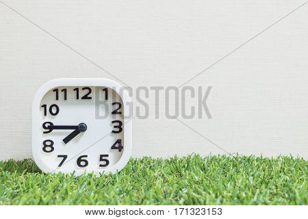 Closeup white clock for decorate show a quarter to eight or 7:45 a.m. on green artificial grass floor and cream wallpaper textured background with copy space