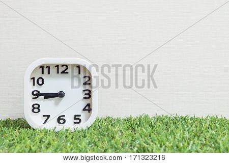 Closeup white clock for decorate show a quarter to nine or 8:45 a.m. on green artificial grass floor and cream wallpaper textured background with copy space