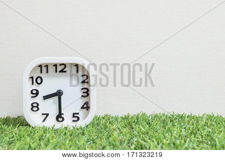 Closeup white clock for decorate show a half past eight or 8:30 a.m. on green artificial grass floor and cream wallpaper textured background with copy space
