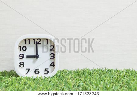 Closeup white clock for decorate in 9 o'clock on green artificial grass floor and cream wallpaper textured background with copy space