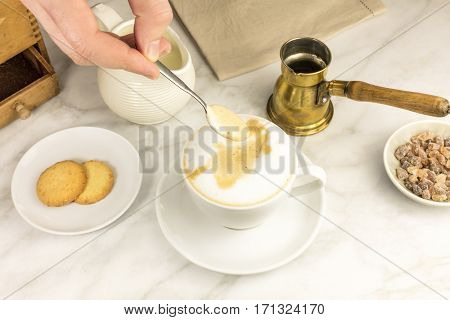Mixing milk and coffee with a spoon, with vintage coffee grinder and pot in the background, butter cookies, and cane sugar. Selective focus