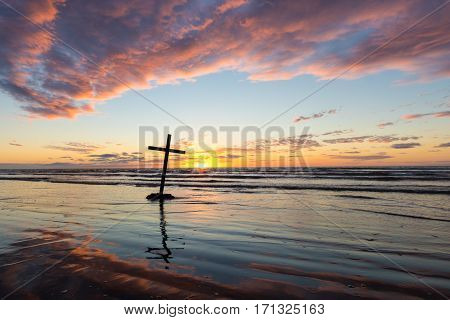 Black cross leaning over on a beach at sunset.