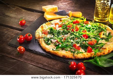 Pizza Caprese with arugula, cheese, yoghurt and cherry tomatoes close up. Homemade delicious vegetarian pizza on wooden table, food.