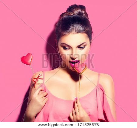 Beauty joyful Young fashion model Girl eating Valentine Heart shaped cookies on sticks in her hands. Love Concept. Beautiful seductive young woman. Valentines Day gift. On pink background