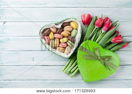 Red tulips bouquet and gift box with macaroons on wooden table. Top view with copy space