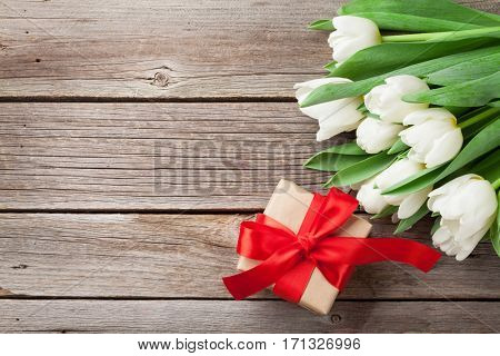 White tulips bouquet and gift box on wooden background. Top view with space for your text