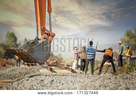Construction sites railway work excavator and busy workers in safety uniform during sunset time