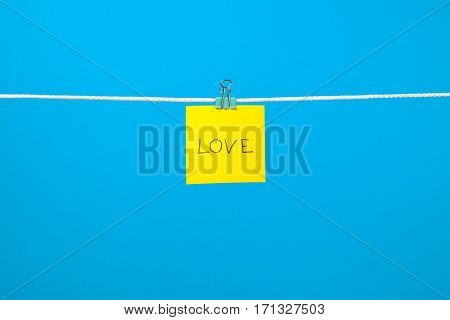 """Yellow Paper Note On Clothesline With Text """"love"""""""