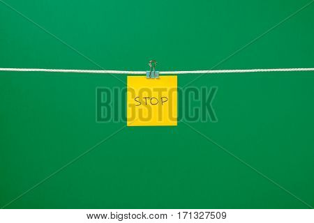 """Yellow Paper Sheet On The String With Text """"stop"""""""