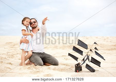 Beach cute girl with her happy father flying kite outdoor coast ocean