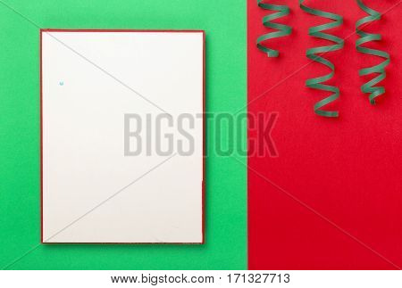Blank card with streamers on a colorful background top view