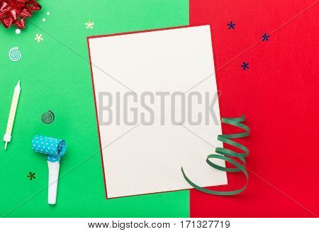 Blank card with different colorful celebration items on a colorful background top view