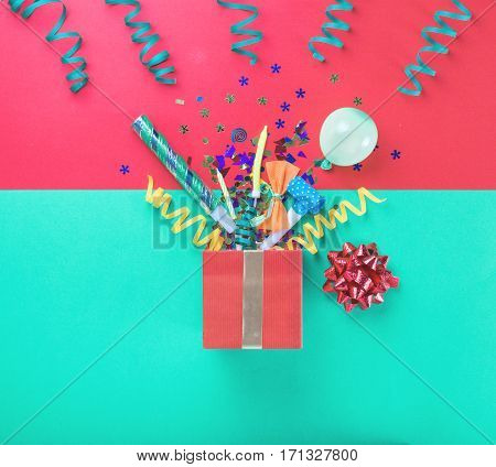 Red gift box with various party confetti balloons streamers noisemakers and decoration on a multicolored background. Top view