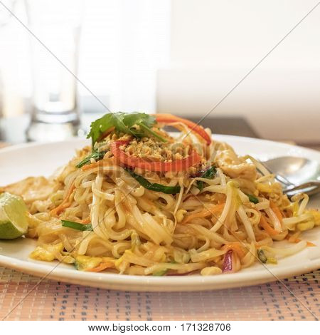 A square photo of Pad Thai Kai, Thailandese noodle dish, served in a restaurant. Selective focus