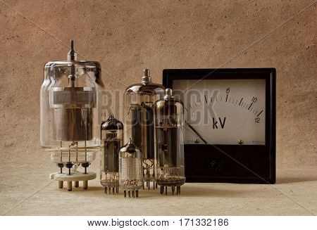 vintage vacuum tubes and voltmeter on kraft paper.electronic background