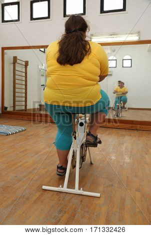 overweight woman exercising on bike simulator from behind
